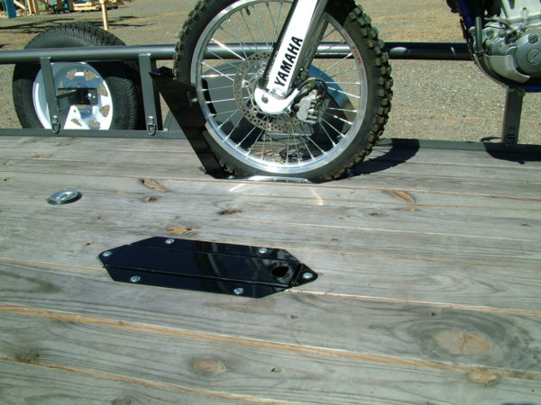 4 inch Wide Popup Wheel Chock folds flat into trailer deck shown in deck of utility trailer with dirt bike in chock