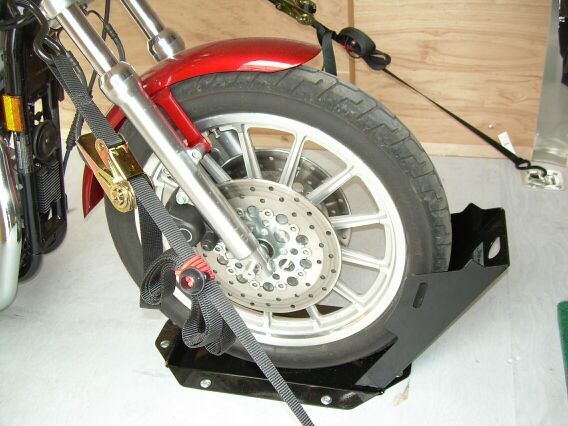 7 inch Wide Popup Wheel Chock shown in enclosed trailer with wheel tied in
